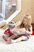 Pretty Little Blonde Girl Sits Near Soft Toy On Carpet In Cozy Room And Reads Book