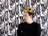 Young Serious Man In Black Shirt And Gold Crown Stands With Near Wall