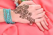 Hands painted with henna on color cloth background