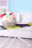 Baskets with laundry and ironing board on home interior background