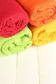 Colorful towels on wooden table close-up