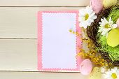 Empty card with easter eggs and mimosa flowers, on white wooden background