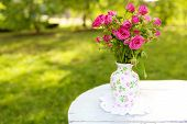 Eustoma flowers in vase on color wooden table, outdoors