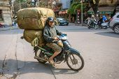 HANOI, VIETNAM - APRIL 2014: Overloaded motorbike on the streets of Hanoi, on April 7, 2014 .