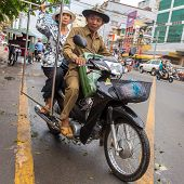 PHNOM PENH, CAMBODIA - MARCH 21: Old couple driving their motorbike in Phnom Penh, Cambodia on March