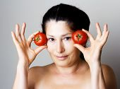 Asian woman showing tomatoes