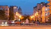 HAVANA,CUBA - JULY 9,2014 : Old american cars at night and the street lamps of El Prado with the Capitol in the background