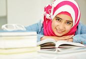 Beautiful Arabic Muslim girl reading on college