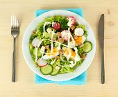 Fresh mixed salad with eggs, salad leaves and other vegetables, on wooden background