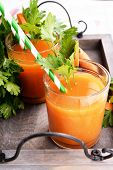 Glasses of carrot juice with fresh carrots and parsley on wooden tray close up
