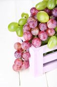 Ripe green and purple grapes in wooden box on wooden table close-up