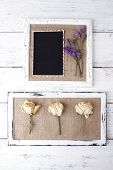 Wooden frames with dried flowers and old blank photo on wooden background