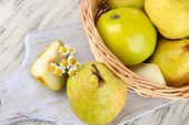 Pears in basket on board on wooden table