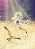 a woman running through a field full of birds and dust toned wit