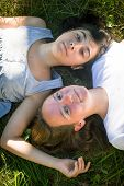 Two young girl lying on grass having good time. (top view)