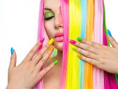 Beauty Girl Portrait with Colorful Makeup, Hair and Nail polish. Colourful Studio Shot of Woman face closeup. Vivid Colors. Manicure and Hairstyle. Rainbow Colors manicure