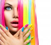 Beauty Girl Portrait with Colorful Makeup, Hair and Nail polish. Colourful Studio Shot of Surprised Woman face closeup. Vivid Colors. Manicure and Hairstyle. Rainbow Colors manicure