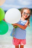Adorable little girl with colorful balloons at beach during summer vacation