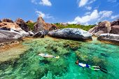 Family of young mother and son snorkeling in turquoise tropical water among huge granite boulders at