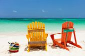 Colorful yellow and orange lounge chairs at tropical beach in Caribbean with beautiful turquoise oce
