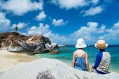 Back view of two kids sitting on granite boulder and enjoying beautiful scenery of The Baths beach area major tourist attraction at Virgin Gorda, British Virgin Islands, Caribbean