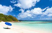 Picture perfect beach with blue umbrella, white sand, turquoise ocean water and blue sky at tropical
