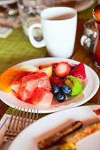 Delicious breakfast with fresh tropical fruits, berries and cup of hot coffee