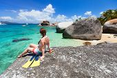 Young woman with snorkeling equipment enjoying view of a tropical beach sitting on granite boulder a