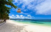 Beautiful tropical beach with white sand and clear turquoise ocean at exotic island in Philippines