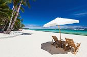 Chairs and umbrella on a beautiful tropical beach with white sand and clear turquoise ocean at exoti