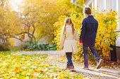 Back view of two kids walking in a beautiful park at sunny autumn day