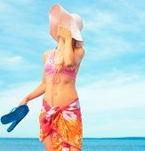 Woman holding her sun hat on the beach.