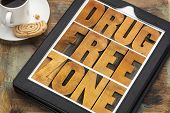 drug free zone word abstract in vintage letterpress wood type on a digital tablet with a cup of coff