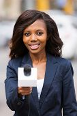 beautiful african news reporter interviewing with microphone