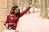 picture of hail  - pretty african woman hailing a taxi cab - JPG