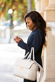 side view of young african woman using smart phone