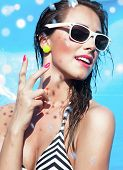 Colorful summer portrait of young attractive happy brunette woman wearing sunglasses at the swimming