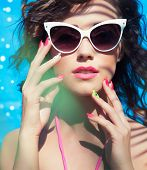 Colorful summer portrait of young attractive brunette woman wearing sunglasses under a palm tree by the swimming pool