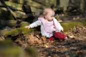 Little Baby Girl Sitting In A Spring Forest