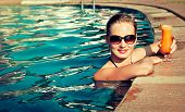 Beautiful girl rests near the swimming pool , sunbathing. Spa treatments.