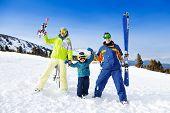 Positive parents in ski masks hold hands of son