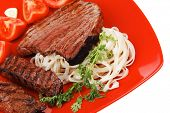 italian food : pasta with tomato and grilled sirloin beef on red plate isolated over white backgroun