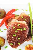 meat savory : grilled beefsteak served with hot cayenne peppers green chives and sweet figs on plate