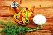 raw peppers sliced on wooden table with sour cream