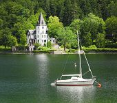 The Grundlsee lake with beautiful castle and sailboat. View from Salzkammergut in Austria, Europe.