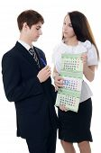 The businessman and businesswoman hold a calendar