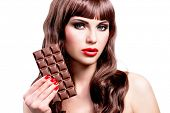 Portrait of beautiful sexy woman with bar of chocolate. Closeup face with bright makeup, isolated on