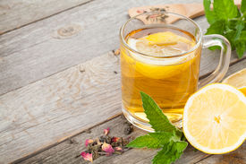 stock photo of mint-green  - Green tea with lemon and mint on wooden table background with copy space - JPG