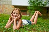 Twelve Year Old Girl Lies On The Grass And Smiling