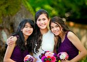 stock photo of biracial  - Biracial bride standing with her two bridesmaids outside smiling and holding flower bouquet - JPG